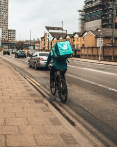 person in green jacket riding bicycle on road during daytime