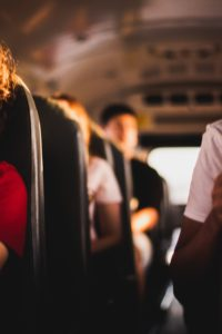 woman in red shirt sitting on bus seat