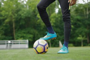 person in blue nike soccer shoes and black pants