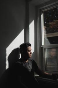 man in black crew neck t-shirt sitting beside window