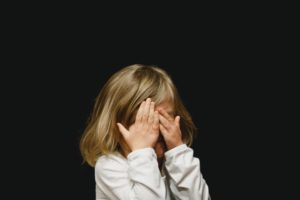 girl covering her face with both hands