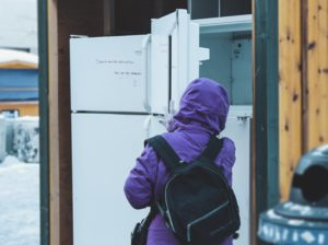 person in purple hoodie standing near white top mount refrigerator