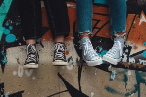 person in blue denim jeans wearing black and white converse all star high top sneakers