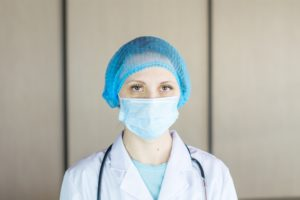 person wearing blue knit cap and white face mask