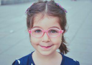 girl in blue and white shirt wearing pink framed eyeglasses